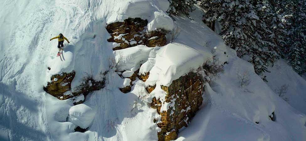 Skier jumping off a large cliff in the backcountry.