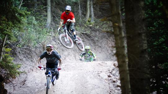 Three mountain bikers hitting a jump.