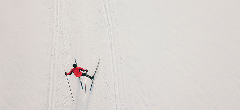 overhead view of a skate skier in action, wearing a red jacket, surrounded by snow