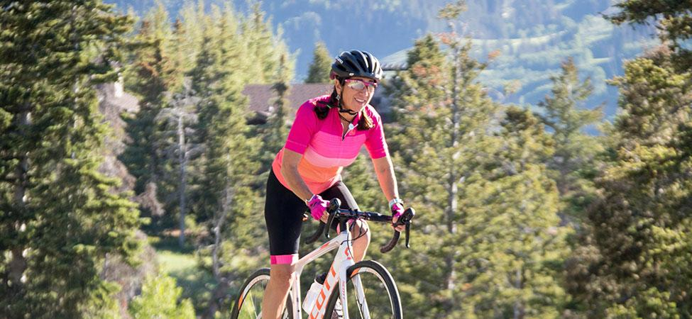 cyclist smiles as she pedals uphill in a sharp-looking kit on a sunny day