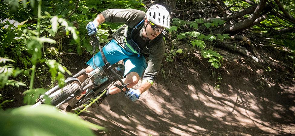 dappled sunlight falls on a mountain biker who leans into a corner