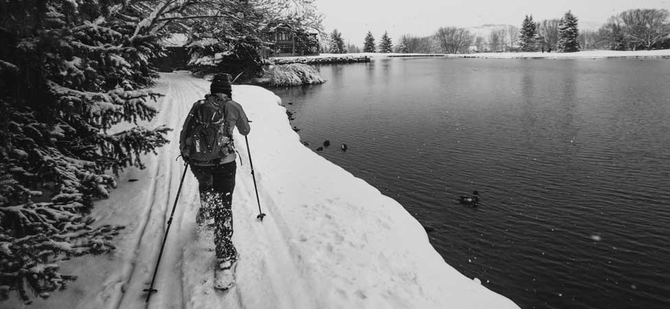 Black and white image of a snowshoer next to a lake in Park City, UT