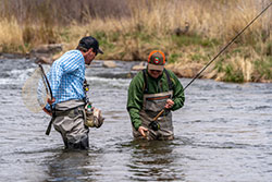 fly fishing guide puts net away, while his client holds the fish he just caught