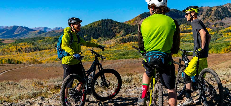 An instructor giving advice to two mountain bikers in Park City, UT