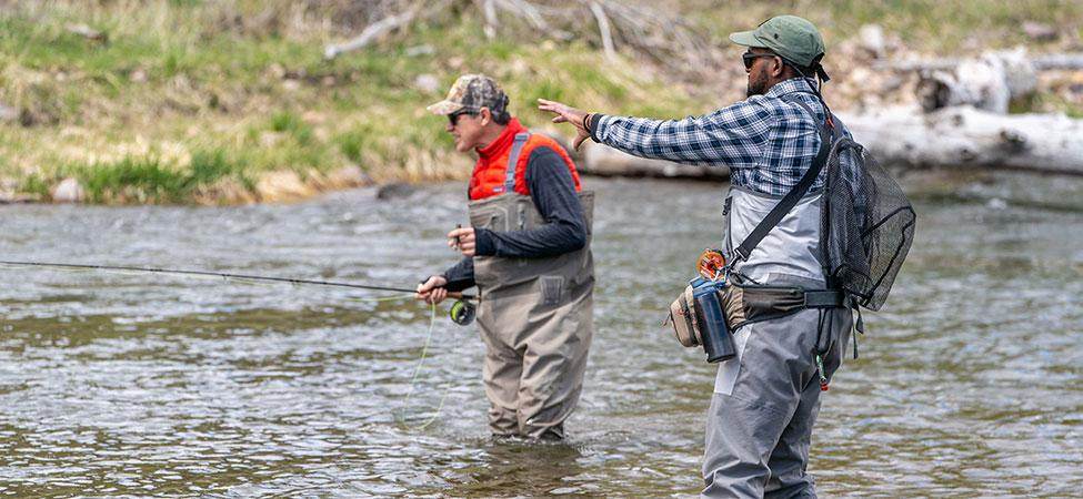 fly fishing instructor gives advice to angler student as they wade in a river