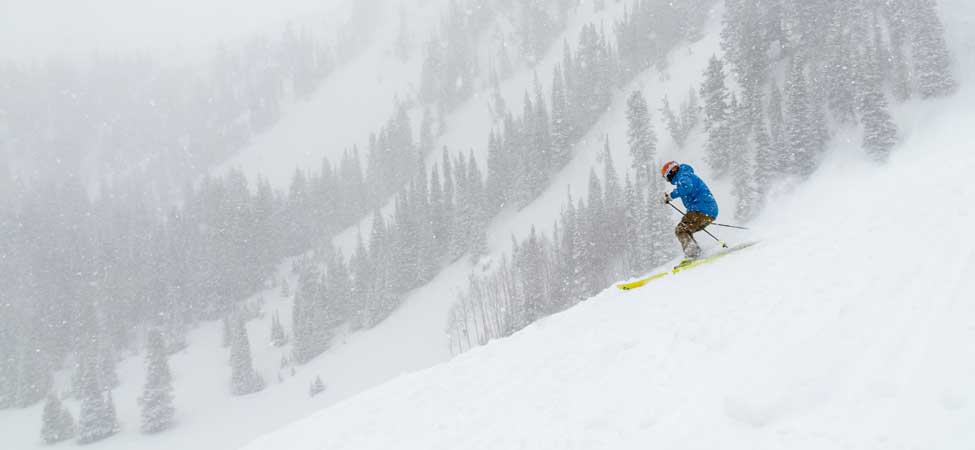 A single skier skiing powder on a stormy day in Park City, UT