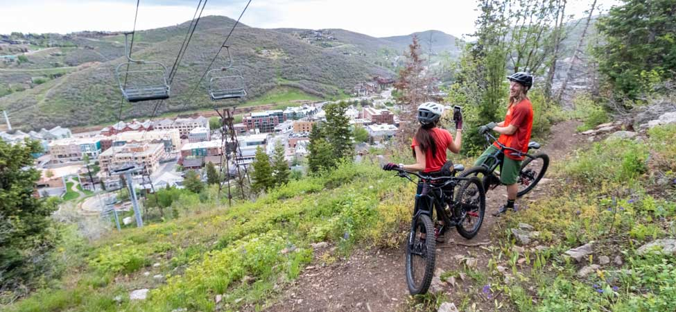 Two mountain bikers overlooking Park City from the Sweeneys Switchback trail