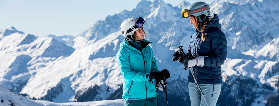 Two skiers talking in front of a mountain landscape.