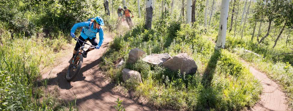 Three mountain bikers navigate a switchback on the WOW trail in Park City, UT.